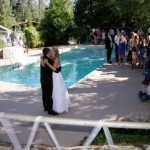married couple and wedding party by the pool