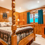 Large bed with wood frame in wood paneled room