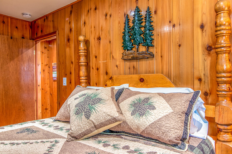 Bedroom from Wildwoods with pillows and wooden tree sculpture on the wall